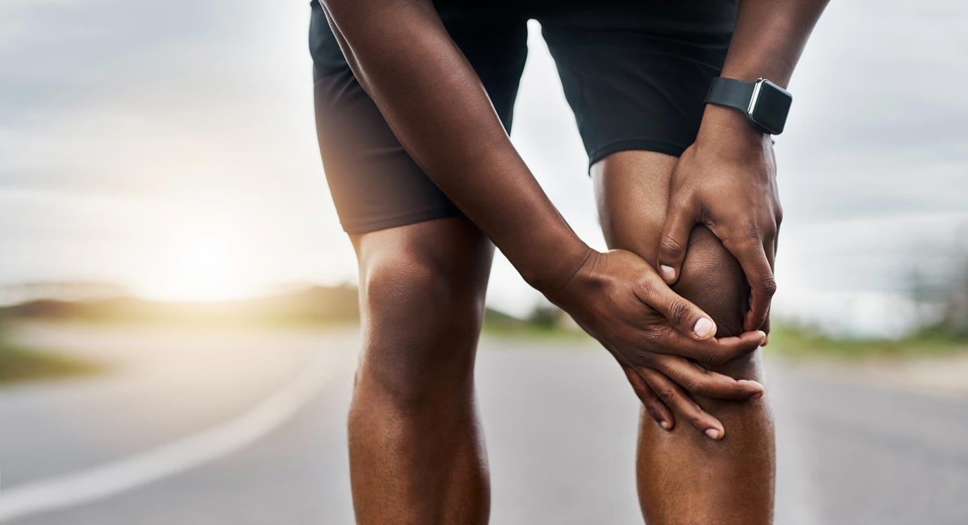 A man using CBD oil to treat joint pain